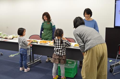 検診の待合会場ではミニ展示会を開催。パルシステムの産直青果を試食する親子。