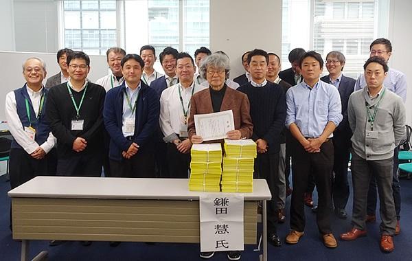 鎌田さん(写真中央)を囲んで都内17ヶ所すべての配送センターのセンター長らとともに。 800枚を超える署名要旨を集めた多摩センターの池田センター長より署名目録を贈呈。