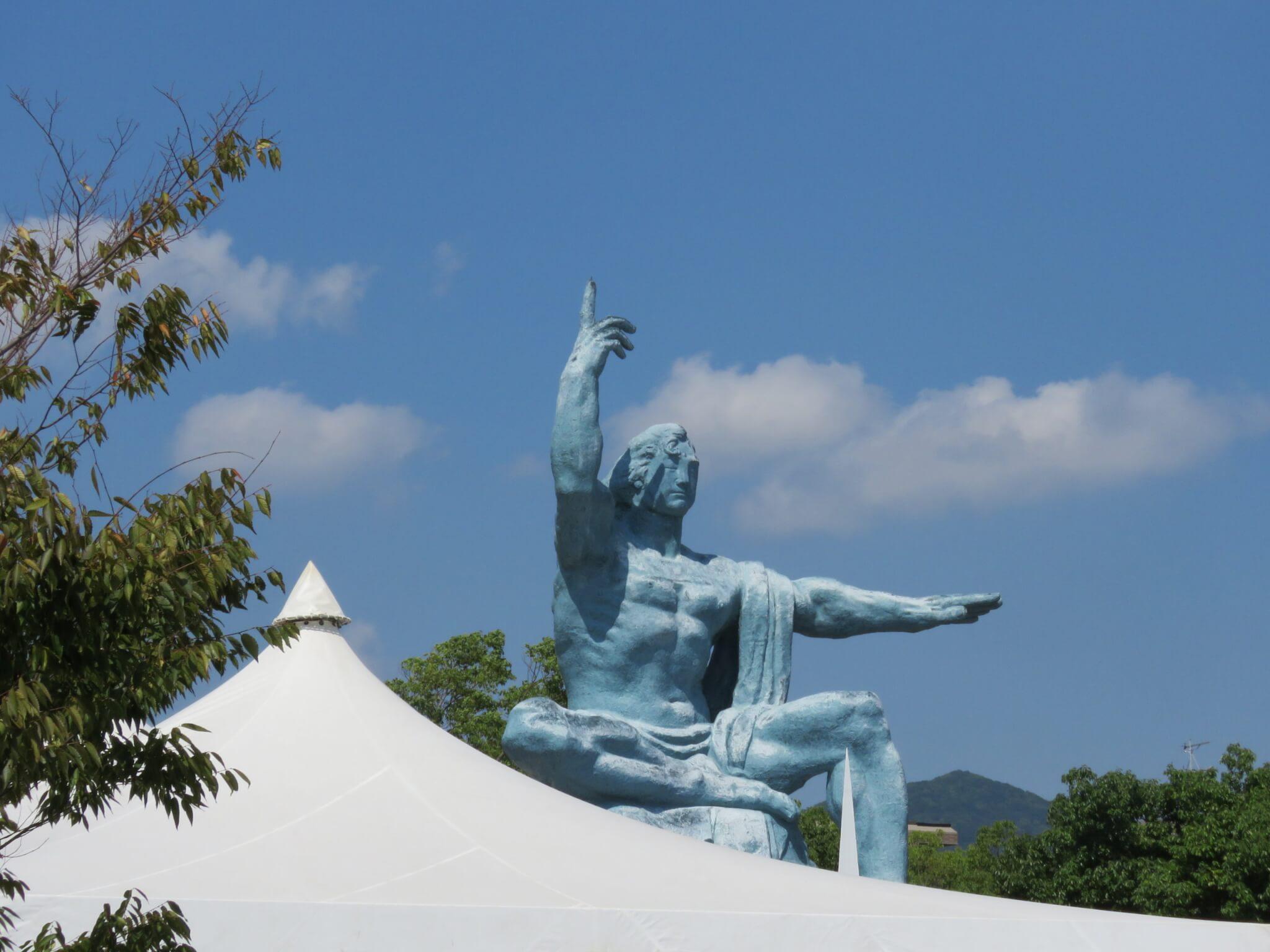 平和祈念像「上に指さした右手は原爆の脅威を、水平にのばした左手は平和を示し、顔は戦争犠牲者の冥福を祈る」作者:北村西聖