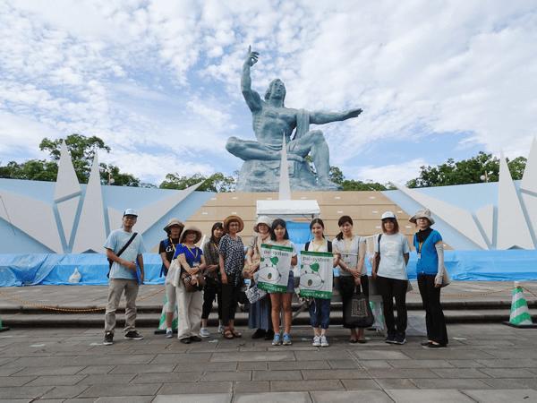 平和祈念像の前で「上に指さした右手は原爆の脅威を、水平にのばした左手は平和を示し、顔は戦争犠牲者の冥福を祈る」作者:北村西聖